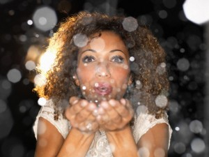 Woman blowing confetti from hands