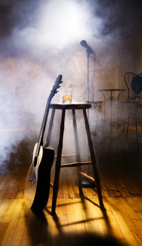 Acoustic guitar leaning against stool in nightclub