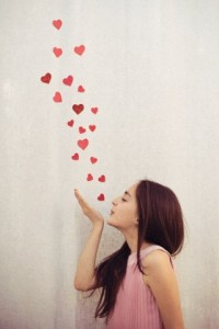 Girl in pink dress blowing hearts