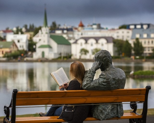 Woman reading next to statue of an Icelandic poet, Tomas Gudmundsson, Reykjavik, Iceland