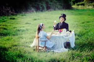 Two girls having tea in a field in France, acting out Alice in Wonderland