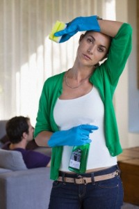 Woman holding cleaning equipment and looking tired with her husband sitting on a couch --- Image by © Fabrice Lerouge/Onoky/Corbis