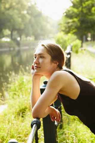 portrait of a young woman daydreaming near a canal