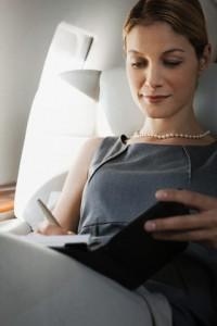 Businesswoman checking her calendar on an airplane